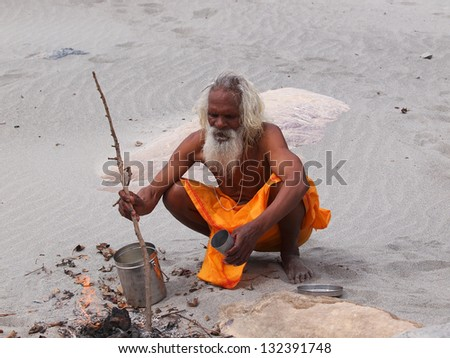 sadhu on the send beach of ganges  cooking dinner