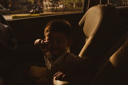 Sadly, the boy was left neglected in the car alone. Crying inside the cabin of a hot and worrisome car : Neglect leads to accidents and negligence concept