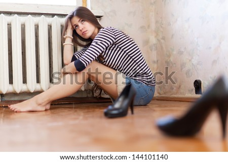 sadness girl sitting on the floor in the corner