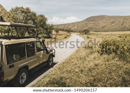 Safari in Hell's Gate national park in Kenya. Off road car, savannah and mountain view. Explore wilderness of Africa. #1490206157