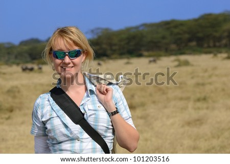 Safari in Kenya. Young blonde woman in sunglasses against African landscape, Naivasha lake national park - stock photo