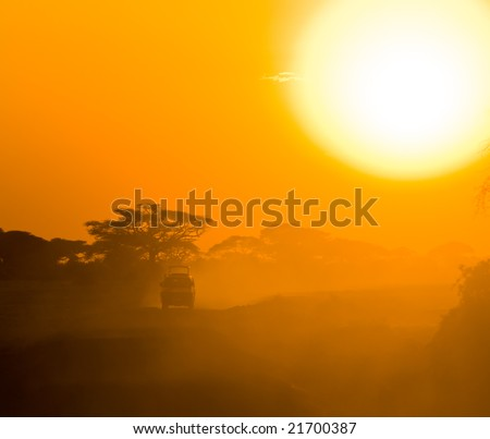 safari jeep driving through savannah in the sunset - stock photo