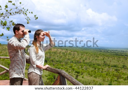 Safari vacation. Young couple in safari clothes observing beautiful national park of Tarangire, Tanzania from balcony in lodge.