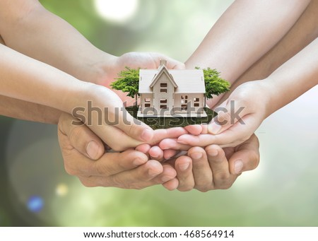 Safe family home model and garden on son/ daughter children & guardian mother/ father hands, blur natural greenery tree planting environment background: World habitat day: Ownership assurance concept
