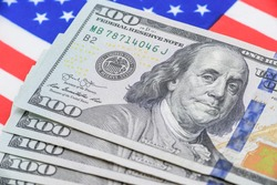 Safe-haven currency for investment, financial concept : US 100 USD dollar banknotes on a flag of USA, depict most popular asset for central bank reserve / global money for using or paying in the world