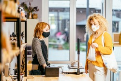 Safe shopping during pandemic. Female seller in protective mask and gloves, apron, stands behind counter, weigh food for a client in zero waste shop.Concept of new rules for business during pandemic.