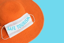 Safe tourism concept: orange summer hat and white medical mask on blue background with copy space for image or text, as a new normal remind for holiday and travel season