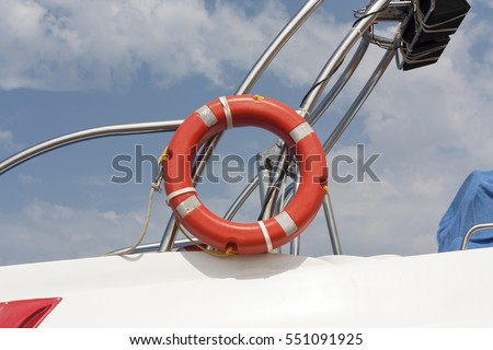Safe water support aid circle with rope. Rescue red life buoy on sky background of ship or boat. Helpful object.