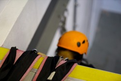 Safe work practices defocused female trained competent person wearing yellow safety helmet using rope protection prevention on sharp edges while descender passing through sharp edges