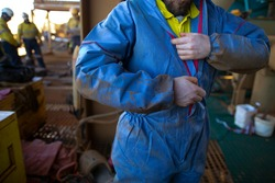 Safe work practices health care  construction worker zipping dress up overall sperm suit body protection uniform prior to work in contaminating area