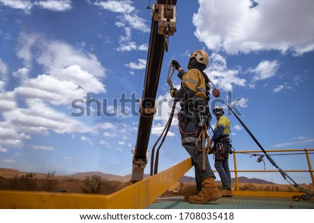 Safe workplace defocused  an inertia reel shock absorbing hook fall arrest device  clipping on rigger harness on the back safety harness hook while working at heights from exposure open edges