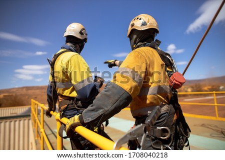 Safe workplace trained supervisor with defocused an inertia reel shock absorbing hook fall arrest device  clipping on the back safety harness hook while working at heights from 2m exposure open edges