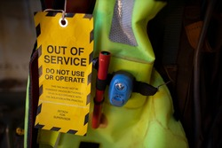 Safe workplaces yellow out of service tag warning sign hanging on damage faulty placing on boat marine safety personal floatation device equipment