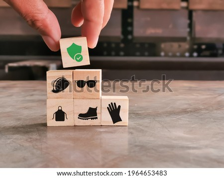 Safety at work concept. Hand putting wooden block with safety icons.