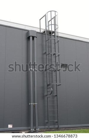 Safety cage ladder on a gray wall. A fixed ladder is a vertical ladder mounted permanently to a structure. These ladders are primarily used to access roofs or other structures for industrial purposes. #1346678873