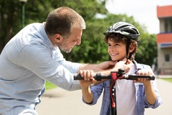 Safety Concept. Close up portrait of smiling adult father putting protection helmet on little boy at park, teaching his brave son to ride electric motorized scooter. Ourdoor Weekend Activity