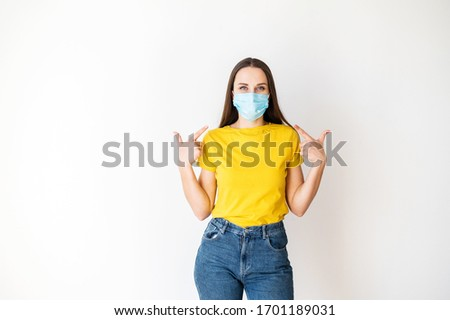 Safety during a pandemic, epidemic, seasonal flu. Positive young woman in a medical mask on her face and in yellow casual tshirt points her fingers to the mask. The call to protect yourself