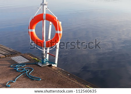 Safety equipment. Bright red lifebuoy on the pier