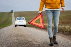 Safety first. Broken car on the road. Driver holding warning triangle. Misfortune on travel. Woman need roadside assistance after car accident