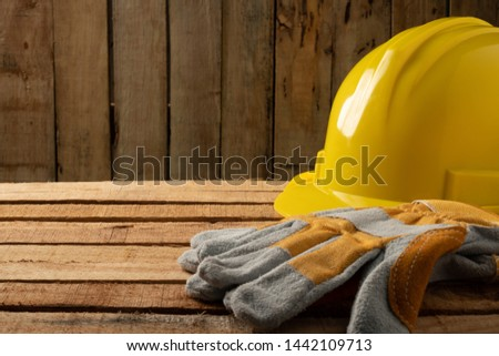 Safety first concept,  personal protective equipment is placed on the wood. Yellow helmet and leather gloves.