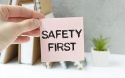 Safety first in unsafe workplace concept photo. Hand of staff is holding the text sign with blurred background of drilling rig or refinery plant equipment at worksite location.