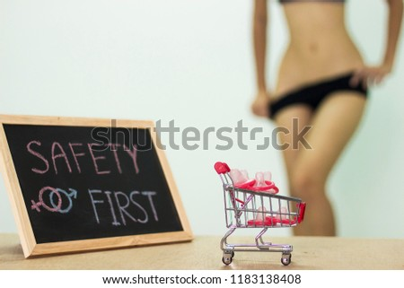 safety first, The blackboard sign reads safety first condom with trolley, female genital concept of an advertisement can be used, About sexuality and the prevention of sexually transmitted diseases. #1183138408