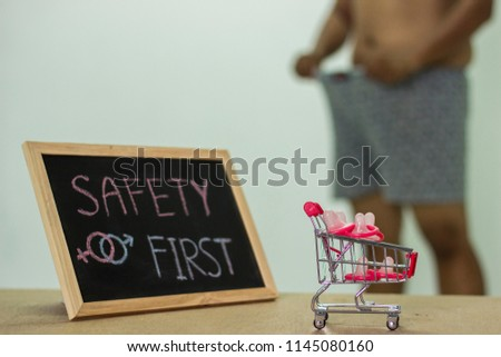 safety first, The blackboard sign reads safety first condom with trolley, male genital concept of an advertisement can be used, About sexuality and the prevention of sexually transmitted diseases. #1145080160