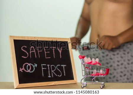 safety first, The blackboard sign reads safety first condom with trolley, male genital concept of an advertisement can be used, About sexuality and the prevention of sexually transmitted diseases. #1145080163