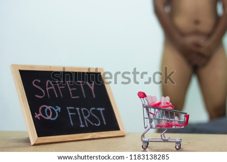 safety first, The blackboard sign reads safety first condom with trolley, male genital concept of an advertisement can be used, About sexuality and the prevention of sexually transmitted diseases. #1183138285
