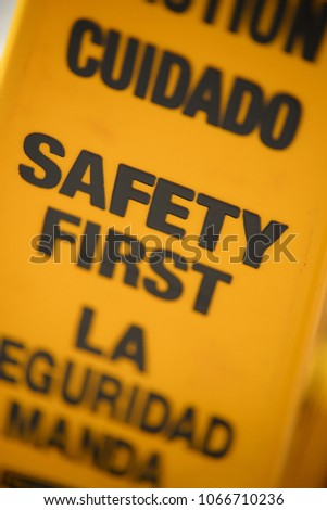 Safety first Yellow cone in English and Spanish #1066710236
