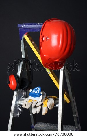 Safety gear kit on step ladder over black - stock photo