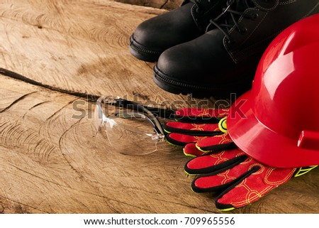 Safety gear kit over wooden background. Red safety helmet or hardhat with safety glasses and other standard safety workwear on wooden board.