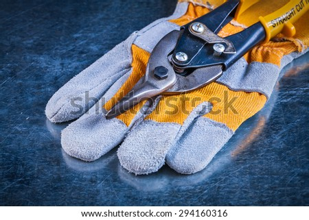 Safety gloves with tin snips on scratched vintage metallic background construction concept.