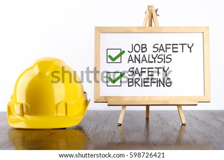 Safety helmet and white board with words Jon Safety Analysis & Safety Briefing,Health and Safety concept.