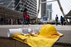 Safety helmet hat, blueprint paper project, gloves, and worker dress on concrete floor at modern city with blurred people. Engineer and construction equipment with copy space for text.