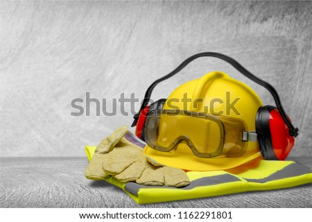 Safety helmet with earphones and goggles on construction background #1162291801