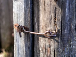 safety in the old days. old gray door locked on a metal hook. Closeup photo