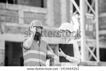 Safety inspector concept. Inspector and bearded brutal builder discuss construction progress. Construction project inspecting. Construction inspection, corrections and fines. Discuss progress project.