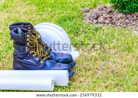 safety shoe and safety helmet on grass background