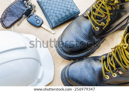 safety shoe and safety helmet,wallet,car Key on Brown Background