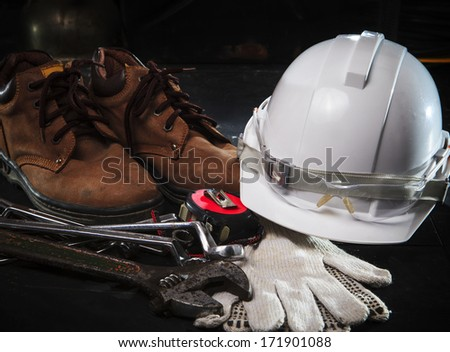safety shoe and safety helmet with construction equipment with low key light use for construction industry topic