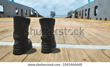 Safety shoes. put on wooden floor of ship deck, with sky and oil platform. As a background, At offshore working area #1045466668