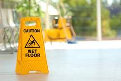 Safety sign with phrase Caution wet floor and blurred mop bucket on background. Cleaning service