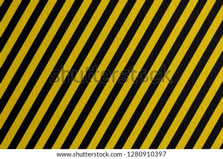 Safety sign yellow and black on mortar texture warning to be careful of the potential danger