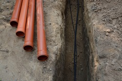 Safety supply to house new insulated internet, gas cord, red metal-plastic tap system construction lay in pit dug in garden. Top view with space for text on grey clay earth. Telecom service industry