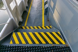 Safety walkway on ships deck. Yellow line walkway. Guided walkway on board. Passenger / contractor footpath on board offshore vessel. Stairs, yellow black step