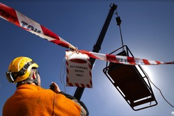 Safety work practice red and white warning danger tag tape sign applying on exclusion dropped zone where rigger operating 2 way radio with crane operator during lifting heavy load at open field