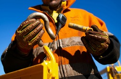 Safety workplace close up image of trained competent rigger high risk worker wearing safety heavy duty glove inspecting D- shape shackle pin prior inserting into crane lifting lug cate during lifting