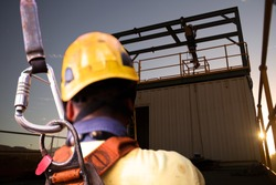 Safety workplace construction worker wearing yellow safety helmet fall arrest PPE harness attached an inertia reel shock absorber device on harness defocused workmate using standing working background