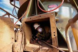 Safety workplace occupational health and safety construction worker wearing a safety white helmet fall protection harness and dust mask protection exiting from confined spaces manhole